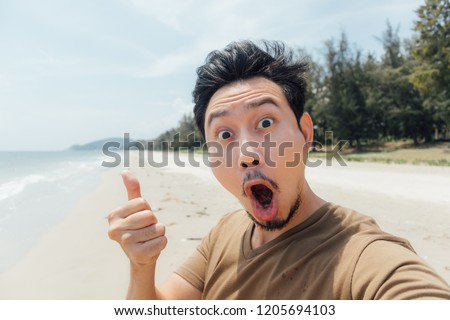Wow and surprised face of asian man selfie himself on the beach of Thailand.