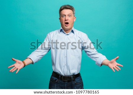 Wow. Attractive male half-length front portrait on blue studio backgroud. emotional surprised bearded man standing with open mouth. Human emotions, facial expression concept. Trendy colors.