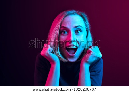 Wow. Beautiful female half-length front portrait isolated on neon studio backgroud. Young emotional surprised woman standing with open mouth. Human emotions, facial expression concept. Trendy colors #1320208787