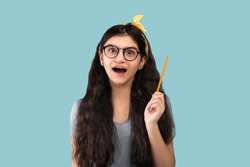 Wow, eureka. Portrait of excited Indian teenage girl having great idea, finding inspiration or solution to problem on blue studio background. Shocked adolescent with open mouth pointing pencil up