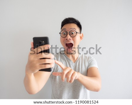 Wow face of Asian man shocked what he see in the smartphone on isolated grey background.