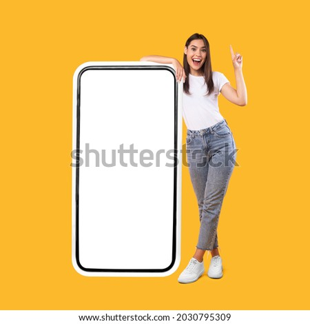 Wow. Happy Woman Leaning On Big Smartphone With Blank White Screen And Pointing Finger Up, Cheerful Lady Recommending New App Or Website, Standing On Yellow Background, Mock Up Image, Full Body Length