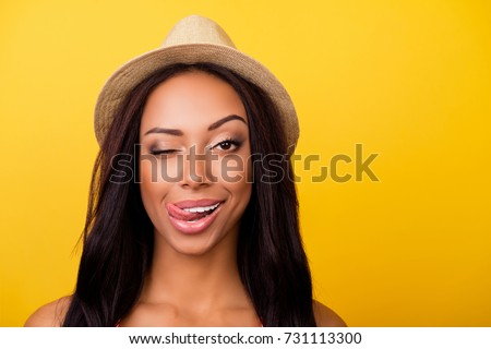 Wow! Healthcare, summer, bodycare, concept. Close up portrait of cheerful coquette afro lady with sticking tongue, looks at camera, wearing beige head wear, so cheerful and carefree #731113300