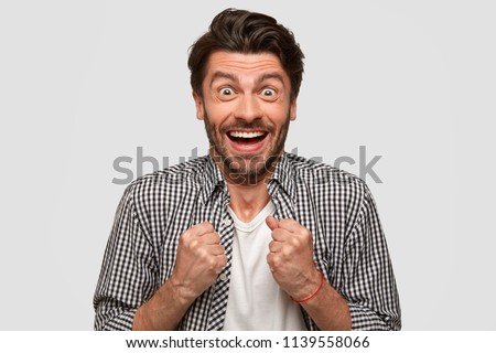 Wow, I done it finally! Glad positive young European male clenches fists with triumph, has happy look, anticipates for something pleasant, reacts on good news, isolated over white studio wall