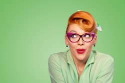Wow, Look here aside. Closeup red head young woman pretty amazed pinup girl in button shirt excited surprised shocked looking up to side retro vintage 50s hairstyle on green wall. Cute face expression
