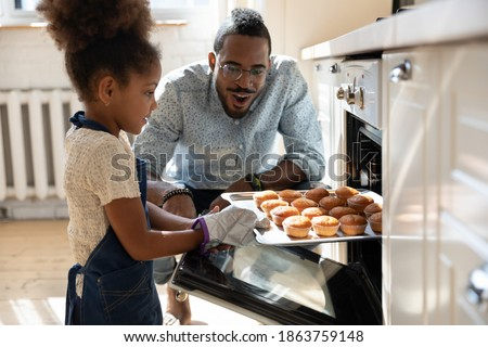 Wow, looks great! Excited caring millennial african dad or grown elder brother watching concentrated small black daughter or younger preteen sister taking pan with self baked tasty muffins out of oven