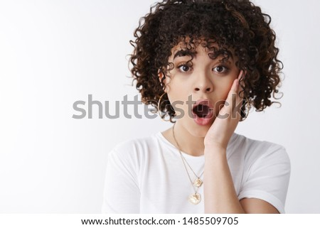 Wow no way, you kidding me. Impressed surprised curly-haired woman learn shocking rumor drop jaw say wow touch cheek thrilled astonished wide eyes camera stunned, white background