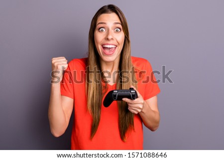 Wow omg i win! Amazed impressed girl play video game get victory scream raise fists wear stylish red t-shirt isolated over grey color background