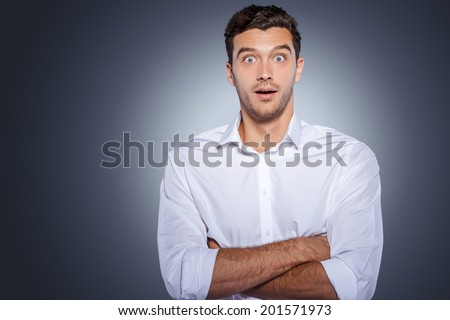 Wow! Surprised young man in white shirt staring at camera and keeping arms crossed while standing against grey background Stock photo ©
