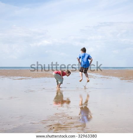 wow, that's high (two boys trying to see who will make a bigger splash  in low tide, Norfolk, UK)