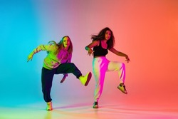 Wow. Two young beautiful girls practice dancing hip-hop in modert sport style clothes on colorful gradient blue orange in neon. Youth culture, movement, active lifestyle, street style, ad