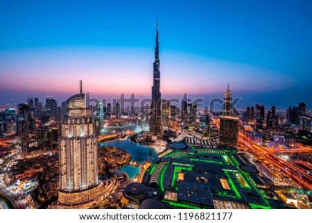 WOW view of Dubai skyline at night. City lights popping. Blue sky. Iconic landmarks. Luxury travel holiday concept.
