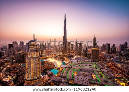 WOW view of Dubai skyline at night. City lights popping. Dancing fountain display. Luxury travel holiday concept.