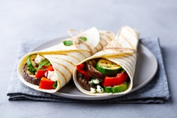 Wrap sandwich with grilled vegetables and feta cheese on a plate. Grey background. Close up.