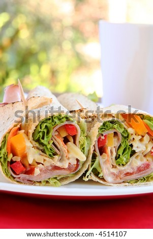 Wrap sandwich with ham and salad, with cup of coffee.  Outdoor setting.