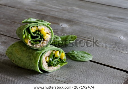 wrap sandwich with pink salmon, conr, and spinach in spinach wrap