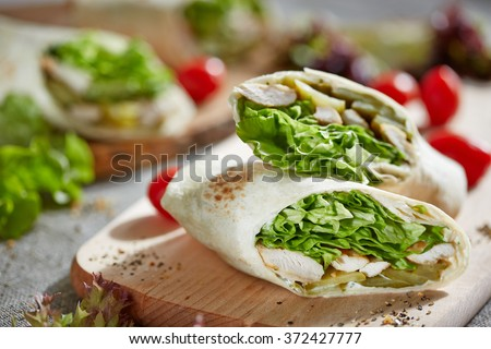 wrap with chicken and lettuce on the wooden cutting board #372427777
