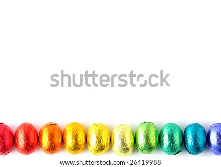 Wrapped chocolate eggs in a row. - stock photo