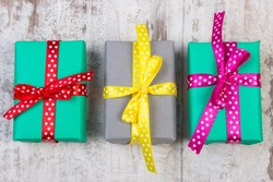 Wrapped colorful gifts for Christmas, birthday or other celebration on old wooden white plank