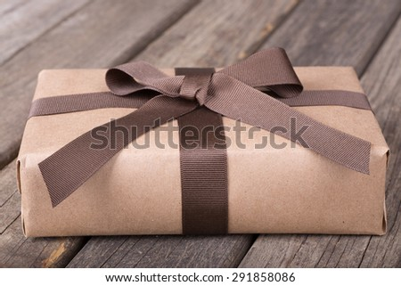 Wrapped gift package on old wood surface