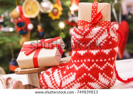 wrapped gift with ribbon for christmas on wooden sled and in red sock on background of - Wooden Sled Decoration Christmas