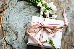 Wrapped gift with snowballs for mothers day on a shabby wooden background