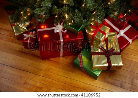 Wrapped gifts under a Christmas tree with room for copy