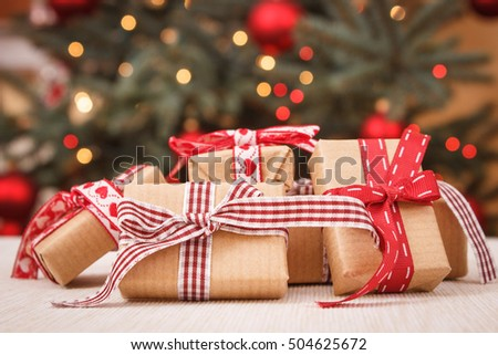 vintage photo wrapped gifts with ribbons for xmas and christmas tree with lights in background ez canvas