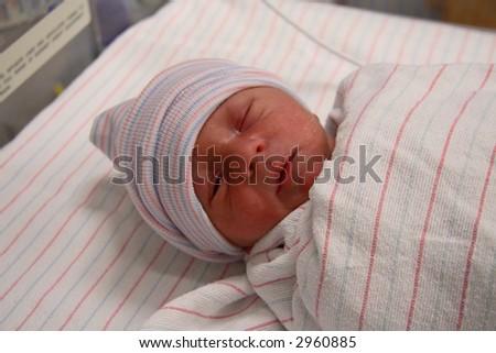 Wrapped newborn in hospital nursery
