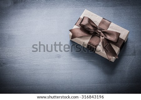 Wrapped present box on vintage wooden board holiday concept.