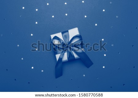 Wrapped present or giftbox toned in color classic blue, top view. Flat lay, giving presents concept. Background for Valentine's Day, Mother's Day.