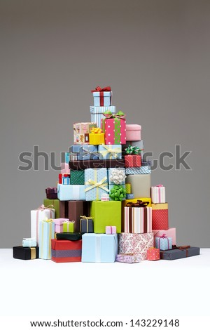 Wrapped presents stacked in the form of a pyramid with cute Gift boxe at the top.  Group of presents. Gift boxes with origami bows.