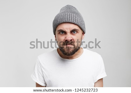 Wrath frustration emotions feelings mental disorder concept. Bearded man pissed off. Frustrated male in grey hat expressing anger. Grimace of anger #1245232723