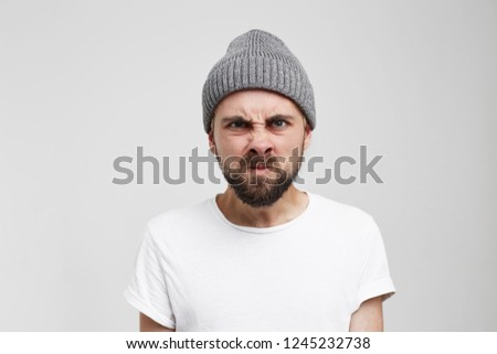 Wrath frustration emotions feelings mental disorder concept. Bearded man pissed off. Frustrated male in grey hat expressing anger. Grimace of anger #1245232738