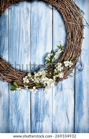 Wreath decorated with spring apple blossom hanging on wooden door