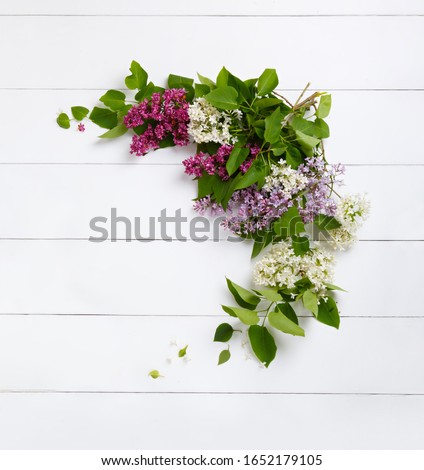 Wreath from purple lilac flowers on white wooden background. Surprise for lovely woman. Natural spring style. Aromatherapy.  Flowers Flat lay, top view. Background with copy space. Spring blossom mood