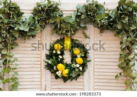 Wreath made of laurel leaves, roses and lemons as decoration on wooden background