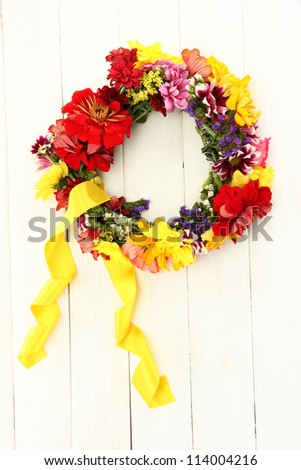 wreath of beautiful summer flowers, on white wooden background