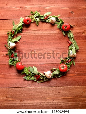 Wreath of green herbs and tomato.on brown wood background
