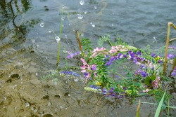 Wreath of multicolored wild flowers on the water surface in summer in Ukraine. Water splashes on the surface of the lake. Copy space.