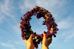 Wreath of Pink Flowers on Blue Sky Background. Female hands holding a Crown of purple flowers on a background of blue sky with white clouds. Hands with a wreath of Midsummer flowers