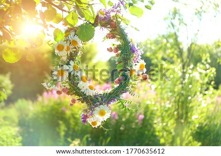 wreath of wild Meadow flower in summer garden. Summer Solstice Day, Midsummer concept. floral traditional decor. pagan witch traditions, wiccan symbol and rituals