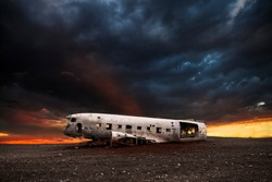 wreck of a white airplane on the black beach of Vik at sunset