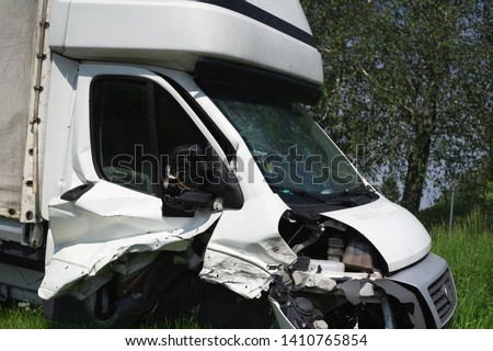 Wreck of vehicle after car crash and accident. Frontal part with of automobile is damaged and needed to repair. Auto is abandoned on the grass.