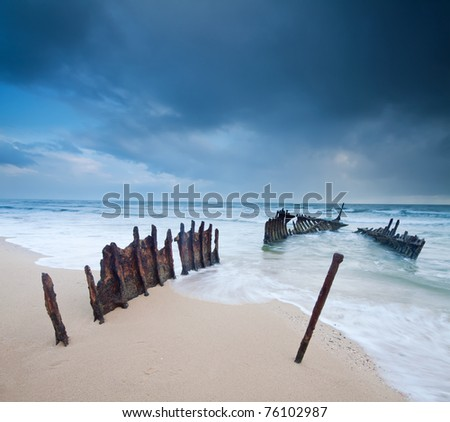 wreck on australian beach at dawn on square format (ss dicky wreck,dicky beach, queensland) - stock photo