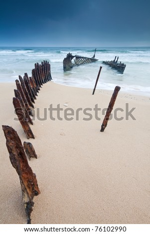 wreck on australian beach at dawn on vertical format (ss dicky wreck,dicky beach, queensland)