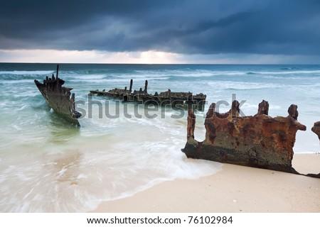 wreck on australian beach at sunrise on horizontal format (ss dicky wreck,dicky beach, queensland)