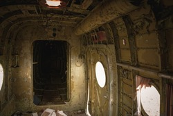 Wreckage aircraft interior. Scary view, old airplane lost at time. Destroyed propeller plane on the field
