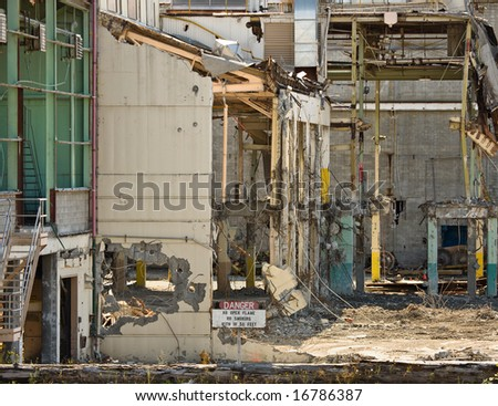 """Wreckage and remains of partially demolished industrial plant, sign in foreground says """"Danger - no open flame, no smoking within 50 feet"""""""