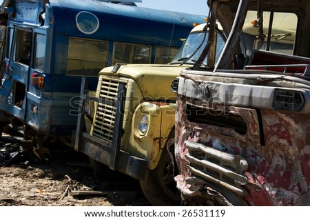 Wrecked buses and truck in a junkyard